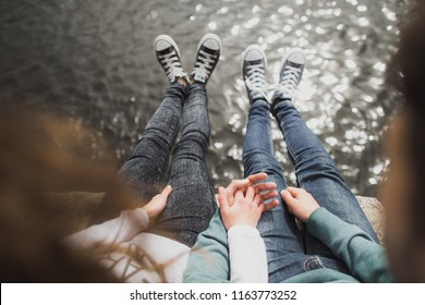Happy young boyfriend and girlfriend having fun outdoors. Couple wearing black and blue canvas sneakers shoes and  denim trousers with skinny fit. Horizontal color photography.