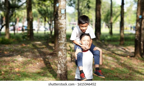 Happy young boys playing at the park. Piggyback around