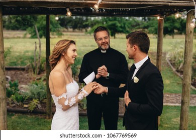 Happy young bride and groom exchanging wedding vows on wedding ceremony in front of priest. Couple reading wedding vows for each other.