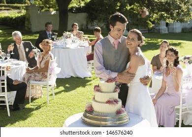 Happy young bride and groom in front of wedding cake while guests sitting in garden