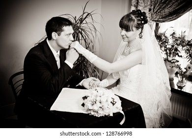 Happy young bride and groom sitting at a table in a cafe on their wedding day. Wedding couple - new family! wedding dress. Bridal wedding bouquet of flowers