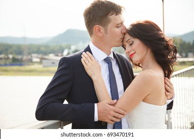 Happy young bride and groom stand on the suspension bridge