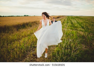 happy and young bride and groom walking in the field