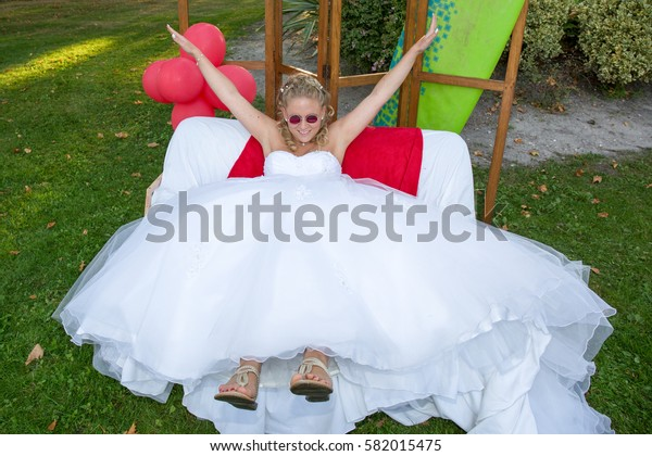 Happy young bride lie on a sofa outdoors