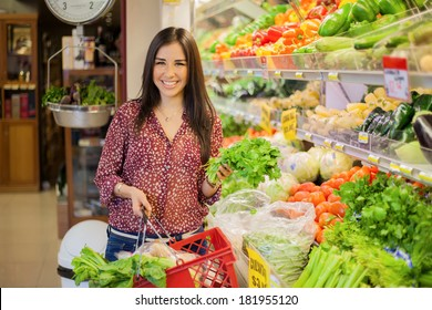 Happy young brunette carrying a shopping basket and picking some vegetables at the grocery store