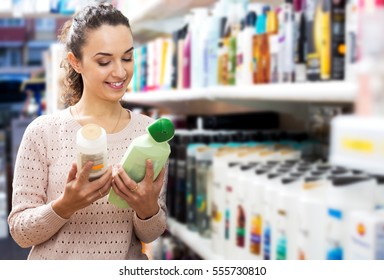 Happy young brunette selecting bottle of shampoo in beauty store