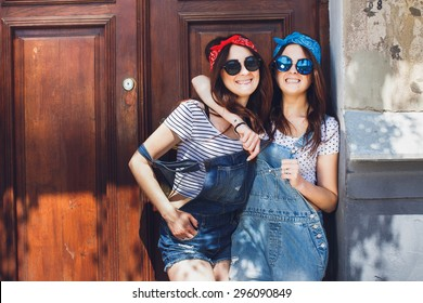 Happy young brunette twins girls, in stylish sunglasses, hugging and smiling. Having great time together. Wearing denim overalls bright bandanas, posing in front of old doors. Outdoors. Summer day.