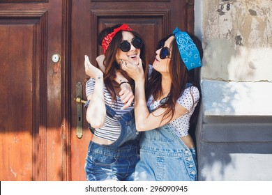 Happy young brunette twins sisters, in stylish sunglasses, hugging and laughing. Having fun time together. Wearing denim overalls bright bandanas, posing in front of old doors. Outdoors. Copy space.