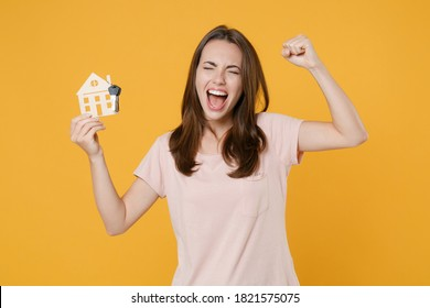 Happy young brunette woman 20s wearing pastel pink casual t-shirt posing hold house bunch of keys doing winner gesture keeping eyes closed isolated on bright yellow color background studio portrait