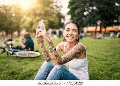 Happy young brunette woman relaxing in a park in Berlin, Germany. Flare backlight filtered image. Lifestyle concept.