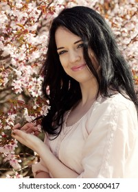 Happy young brunette woman in spring flowers garden lifestyle portrait.