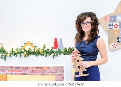 Happy young brunette woman standing in Christmas decorated room and holding a small tree.