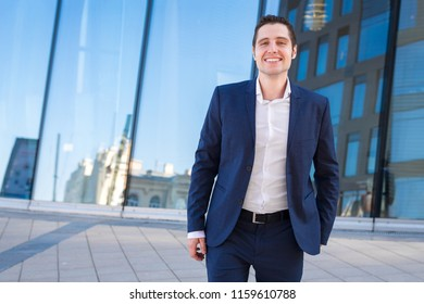Happy young businesman is smailing after successful deal on blue background