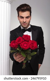 Happy young business man giving you a bouquet of red roses while looking at the camera.