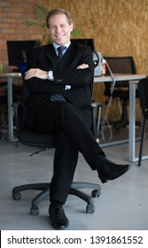 happy young business man with hands crossed sitting on a chair and smiling with a wide bright smile. He looks successfull.The businessman is wearing a black suit and a tie. He is sitting in his office