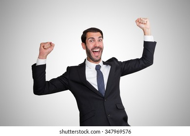 Happy young business man with hands closed at head level.