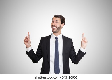 Happy young business man pointing with both fingers.