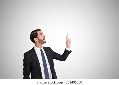 Happy young business man pointing up with his left hand.