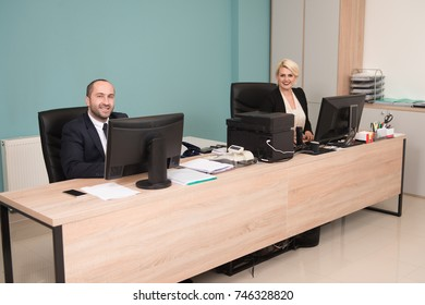 Happy Young Business Man And Woman Work In Modern Office On Computer