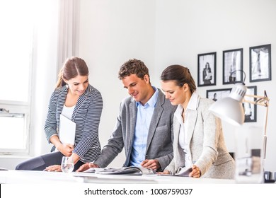Happy young business people discussing over brochure at office desk