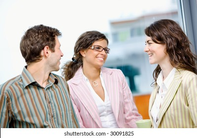 Happy young business people drinking coffee and talking at office in front of window, smiling.