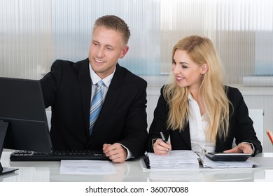 Happy young business people with paperwork discussing over computer at desk in office