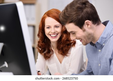 Happy young business team consisting of an attractive redhead woman and man sitting working together in the office