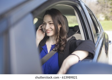 Happy young business woman driving a car