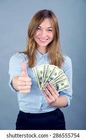 Happy young business woman with gesture thumbs up. Beautiful smiling business woman standing against blue background. Thumb up concept. Woman holding a hundred dollar bills USA. Victory, success.