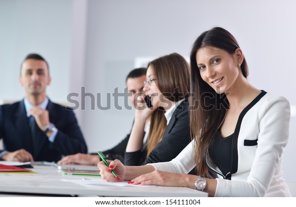happy young business woman  with her staff,  people group in background at modern bright office indoors
