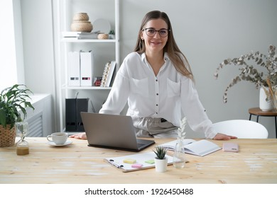 Happy young business woman looking camera leaning on her desk home office.