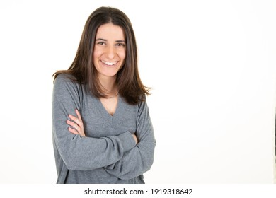 Happy young business woman posing arms crossed isolated white wall background aside copy space in grey sweater