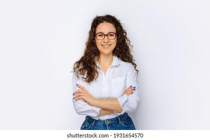 Fröhliche junge Geschäftsfrau, die sich einzeln auf grauem Hintergrund posiert