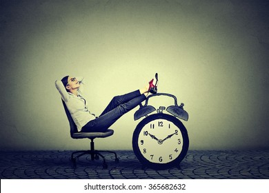 Happy young business woman relaxing sitting in her office. Stress free time management concept