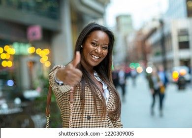happy young business woman showing a thumbs up