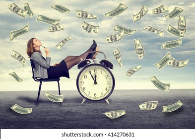 Happy young business woman sitting on a chair under a money rain .