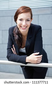 Happy young business woman smiling on a railing