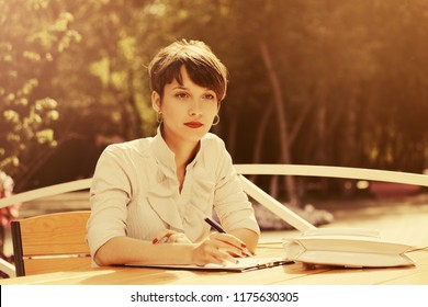 Happy young business woman working at sidewalk cafe Stylish fashion female model with pixie hair style wearing white shirt