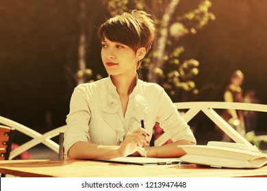 Happy young business woman working at sidewalk cafe Stylish fashion female model in white shirt outdoor