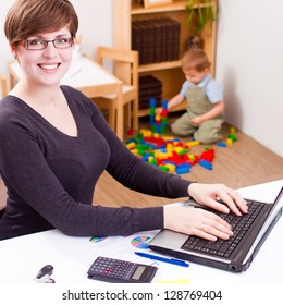 happy young business woman working on a laptop with her child playing at the back