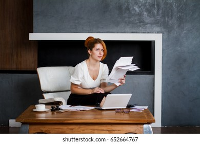 Happy young business woman works sitting in a chair in the office