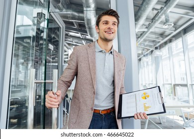 Happy young businessman with business plan on clipboard entering the door in office