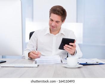 Happy Young Businessman Calculating Bills At Desk