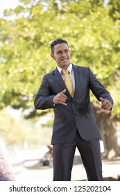 Happy young businessman at the city park