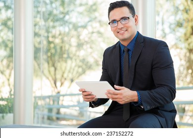 Happy young businessman doing some social networking on a tablet computer and smiling