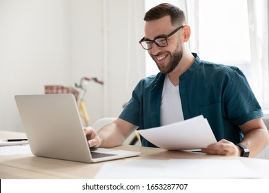 Happy young businessman in eyeglasses working on computer at modern office. Smiling company employee in eyeglasses holding paper documents, chatting online with clients on laptop at workplace.