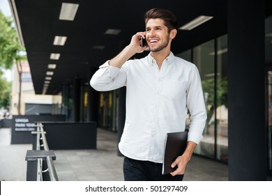 Happy young businessman with folder walking and talking on cell phone near business center