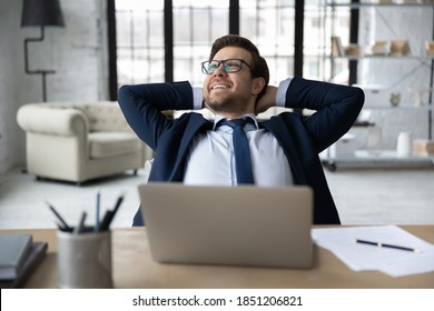Happy young businessman in formal wear and eyeglasses stretching back with folded hands behind head, relaxing at modern workplace, finishing workday or meeting deadline, feeling no stress at work.