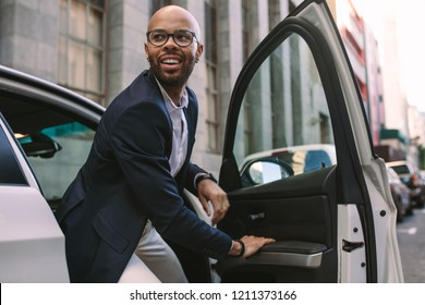 Happy young businessman getting down from car on road. African man in suit stepping out of a his vehicle.