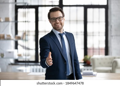 Happy young businessman in glasses looking at camera, reaching out hand making welcoming gesture or ready handshaking with partner or colleague, smiling banker proposing good deal to client.